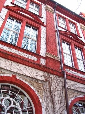 Dziedziniec Ossolineum - czerwony budynek otoczony żywopłotem